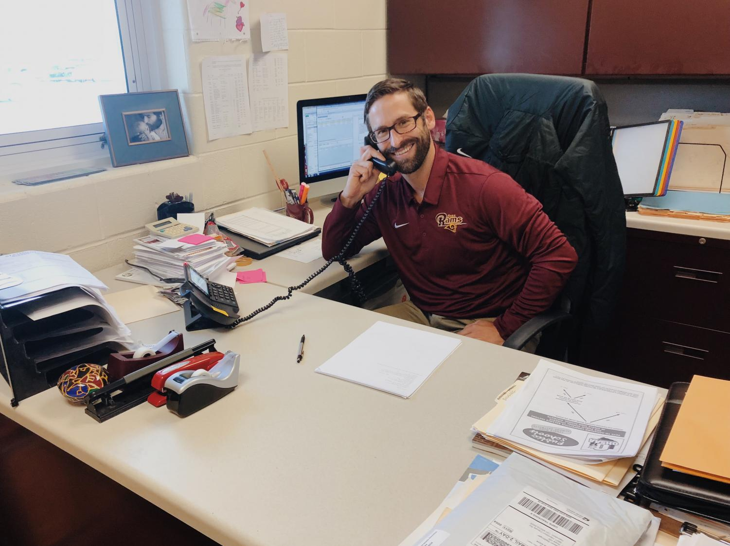 Athletic Director, Mr. Jake Richards, takes a phone call.