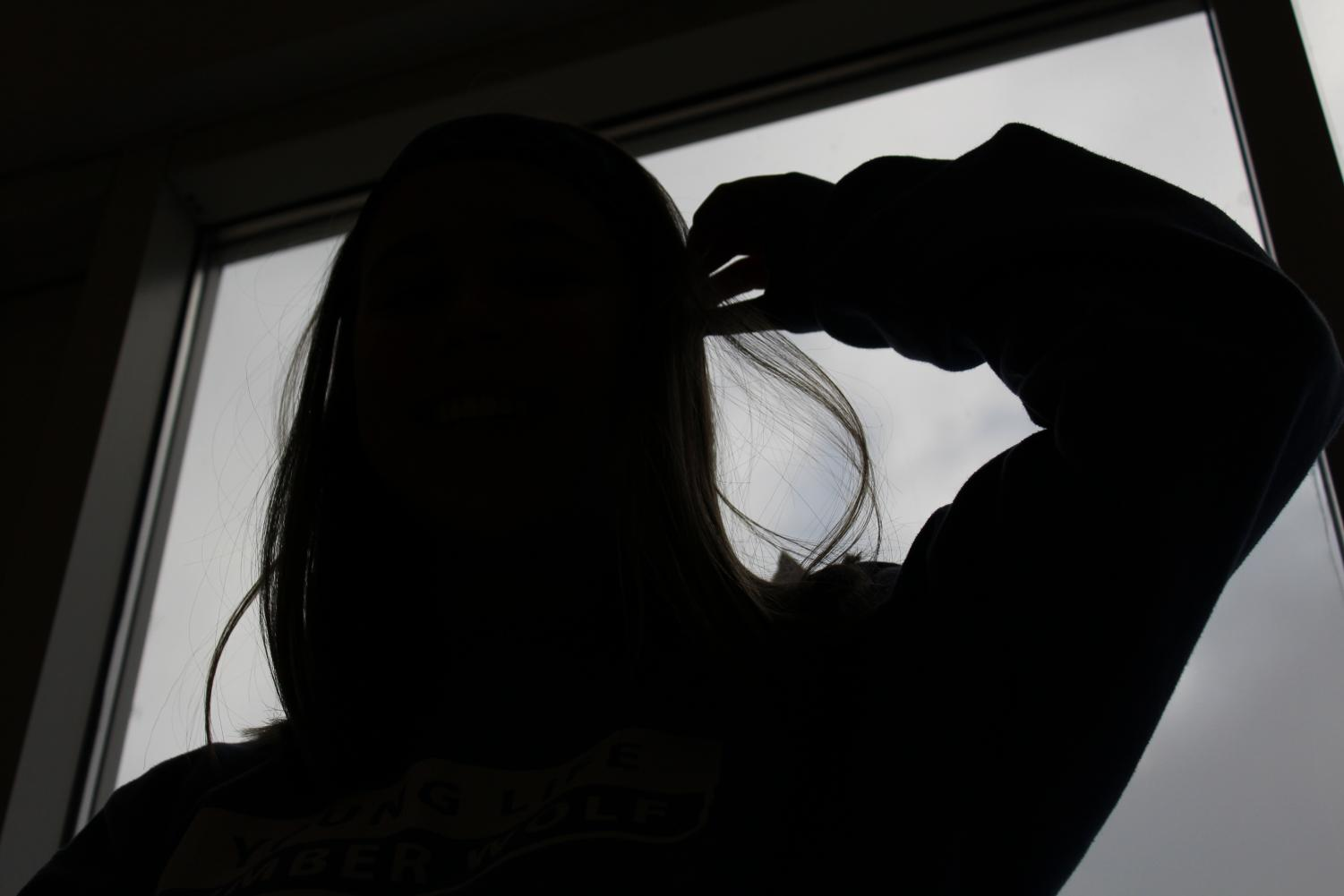A student embracing being alone by posing in front of a window with a dark shadow outline of the student.
