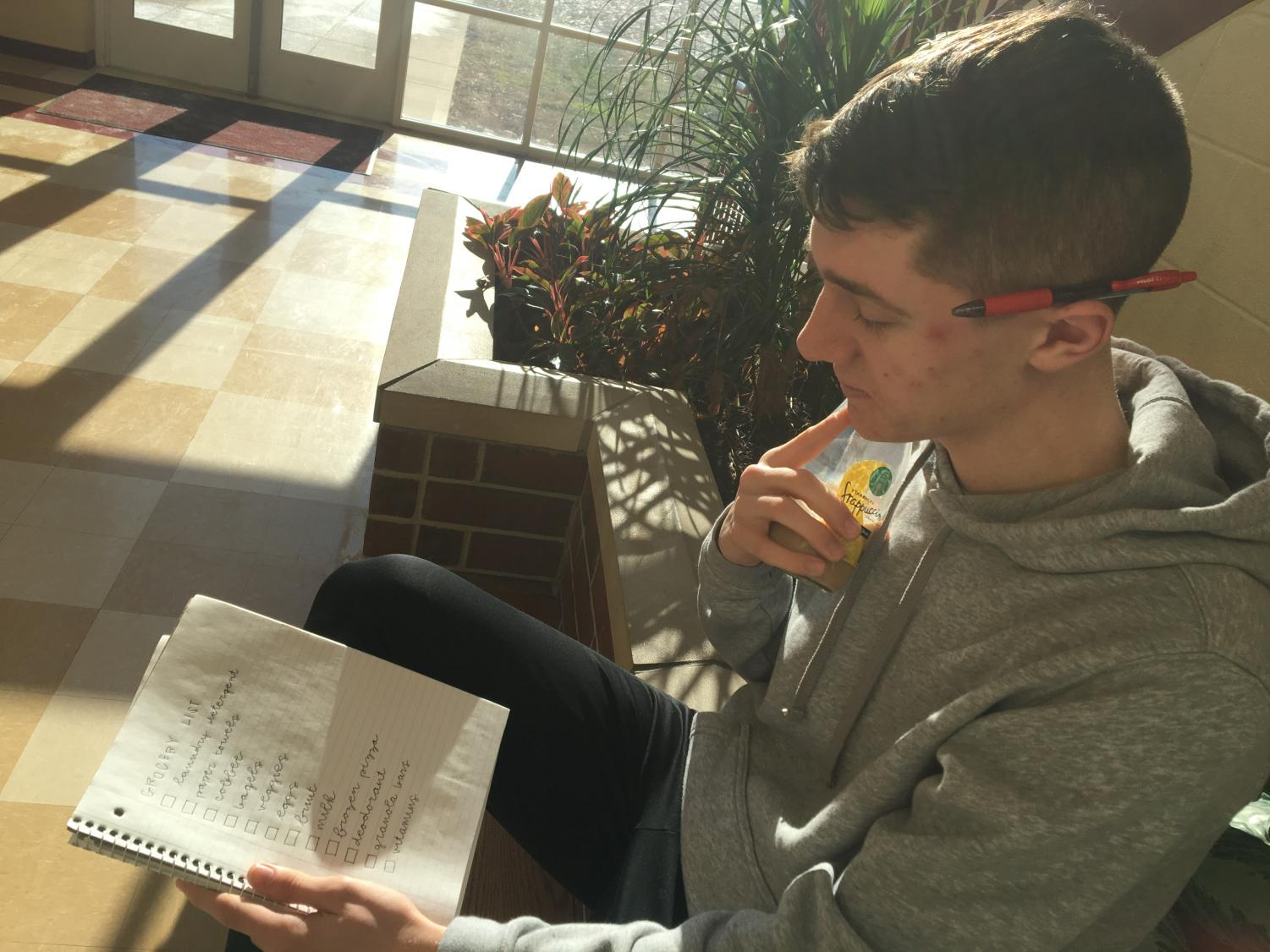 Senior Jacob Butzin examines his grocery list while enjoying coffee.