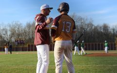 Coach Ben Toerner gives junior Ethan Hall advice before his upcoming at-bat after a Harrison pitching change.