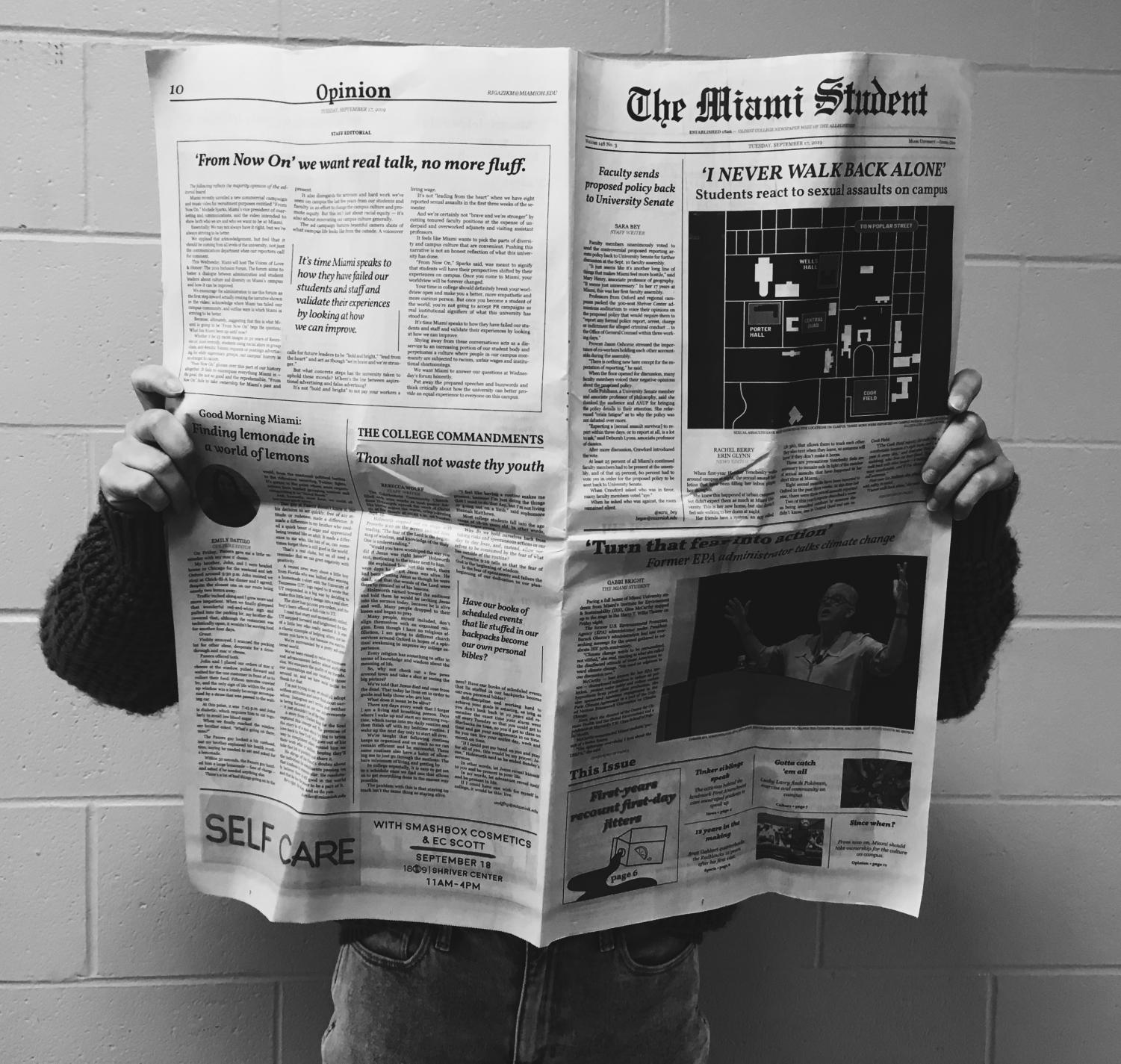A student displays a printed copy of a local university's newspaper,