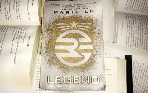 Legend by Marie Lu sits at the top of a pile of unique books.