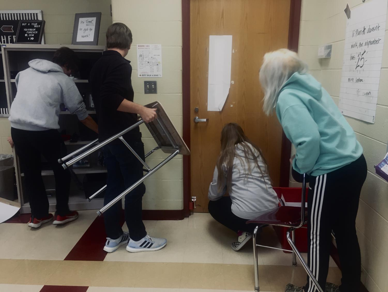 RHS students begin barricading a classroom door to practice ALICE training.