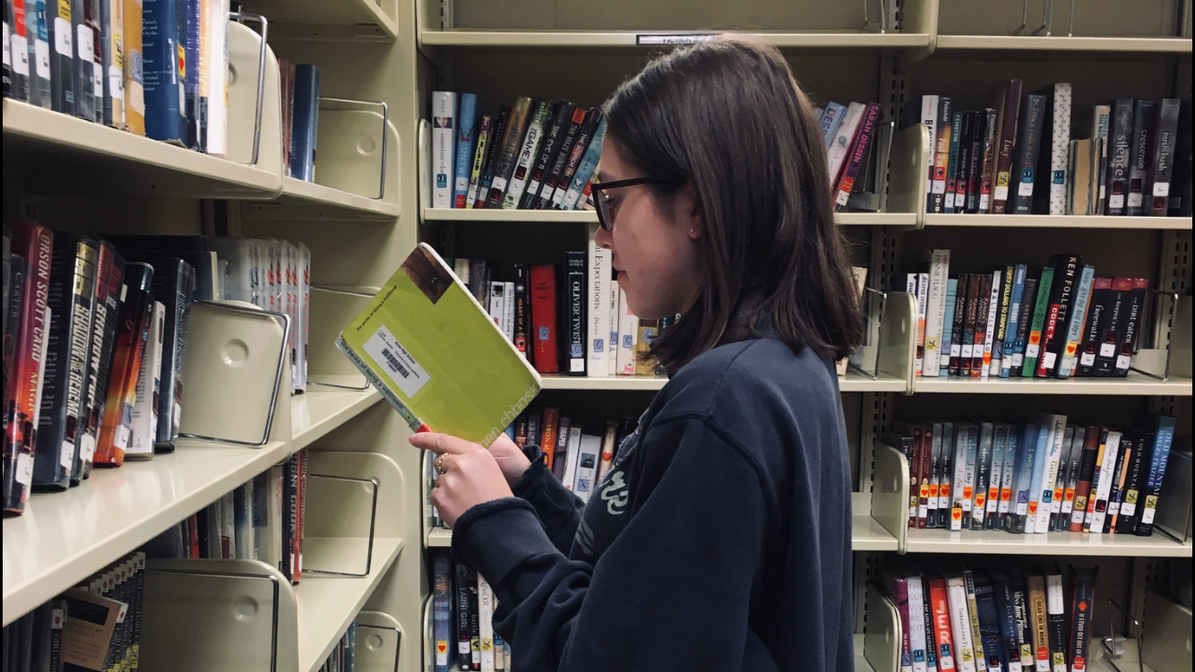 Senior Juliana Curtis picks up a copy of The Perks of Being a Wallflower while browsing the media center.