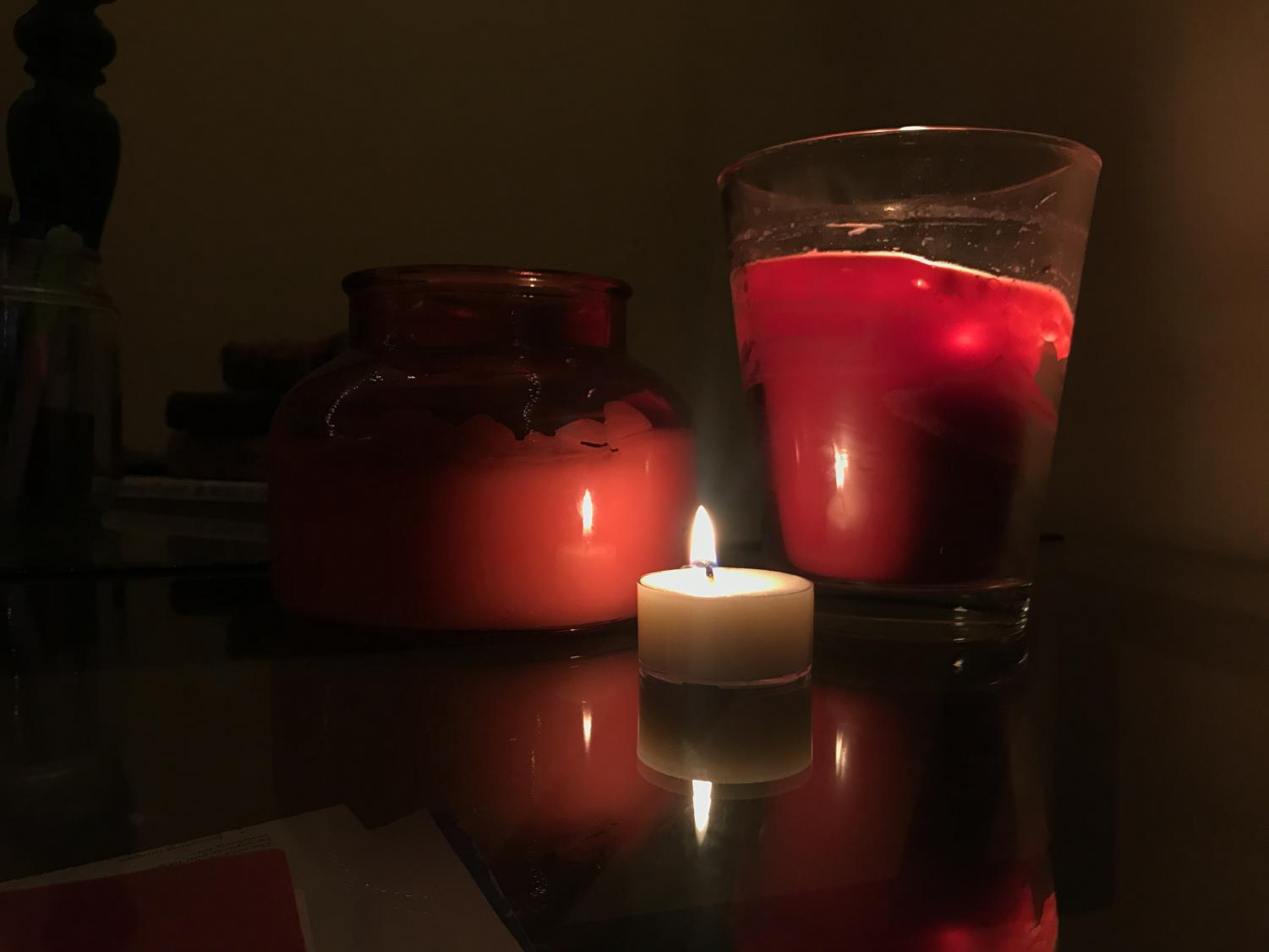 A small, homemade candle burning in front of two larger candles.