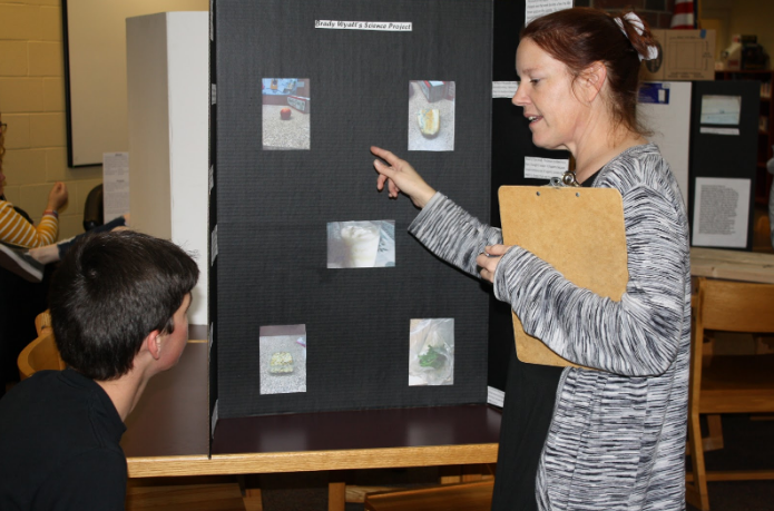 Science teacher Mrs. Beth Mitchell discusses with Sophomore Brady Wyatt his science fair project