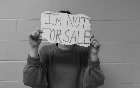 A student stands holding a sign saying