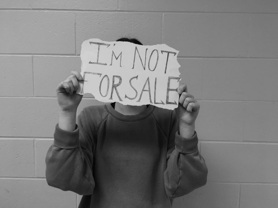 A+student+stands+holding+a+sign+saying+%22I%27m+not+for+sale%22+to+symbolize+the+human+trafficking+issue+plaguing+society