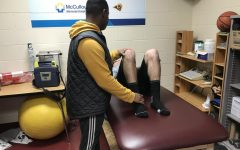 Khari helps an athlete with his knee.