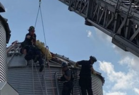 Jay Butterfield is rescued by several fire department officials from a grain bin in Ross, OH.