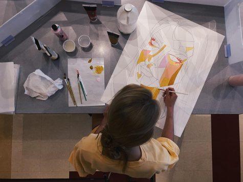 Senior Skylar Angel starting to fill in color on her art piece in Mrs. Baker