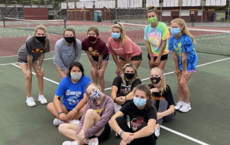 After a tough practice the girls' tennis team poses for a picture.