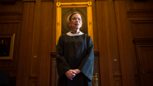 Ruth Bader Ginsburg stands before the US Supreme Court.