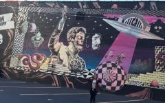 Trinity Stewert stands beside a mural in downtown Cincinnati.
