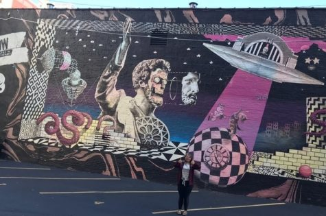 Trinity Stewert stands beside a mural in downtown Cincinnati.