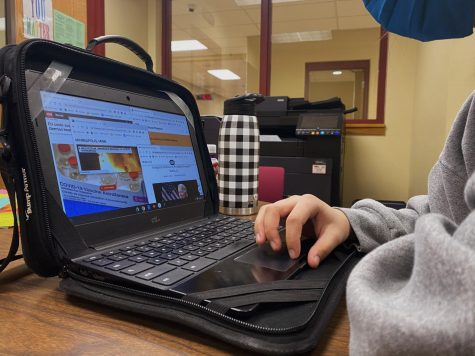 RHS student browses her chromebook, looking at the latest news updates going on around the world.