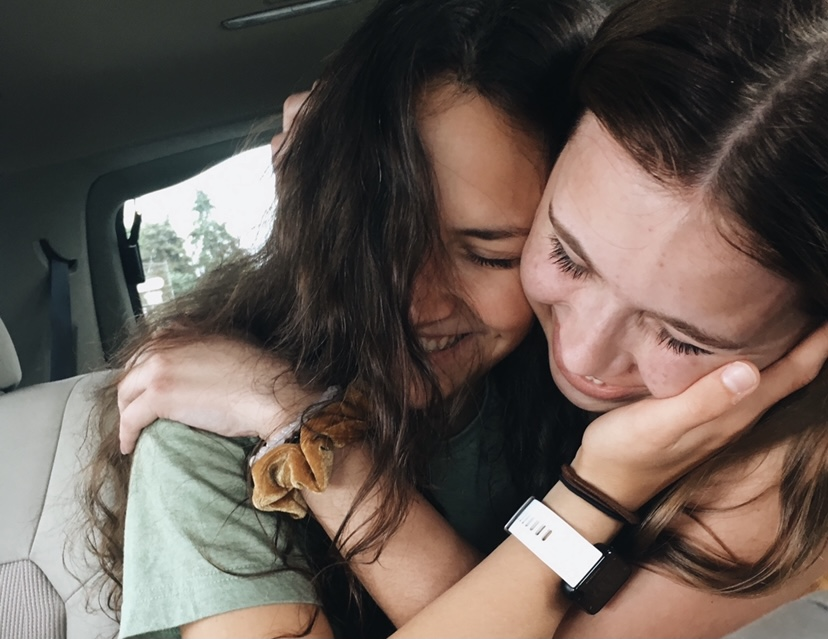 Two friends share an embrace after spending time apart.