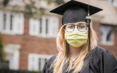 An unknown senior shows off her cap, gown, and masks during her graduation.
