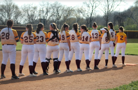 The JV softball team lines up for their pregram routine.